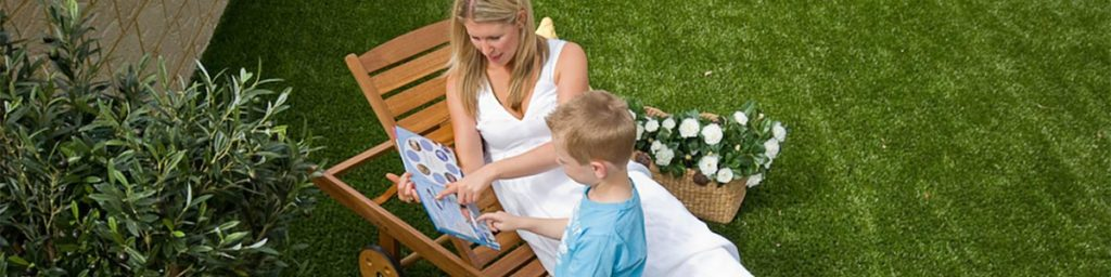 Mother and Son Reading a Book in Backyard of Synthetic Lawn